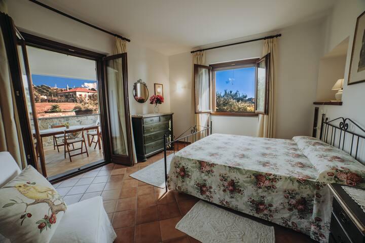 Camera da letto, da cui si accede al terrazzo, arredata con letto matrimoniale in ferro battuto e mobili in stile (armadio, comò e comodini).
