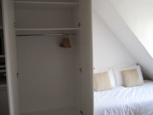 A big wardrobe by the bed has lots of space to store your clothes & luggage