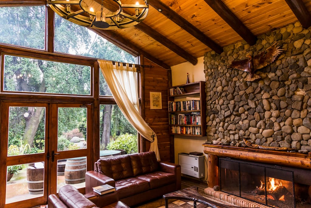 Shared living space with stone fireplace and garden views.