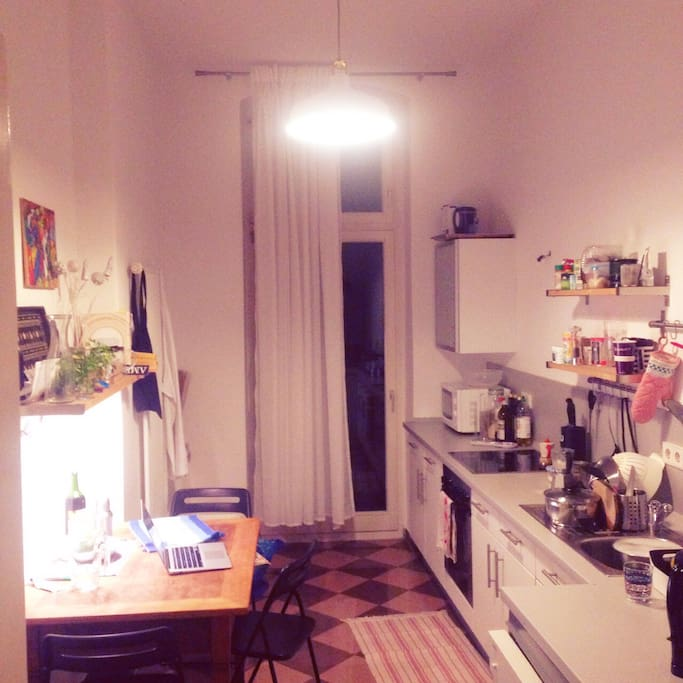 Well equipped kitchen with balcony (at night).