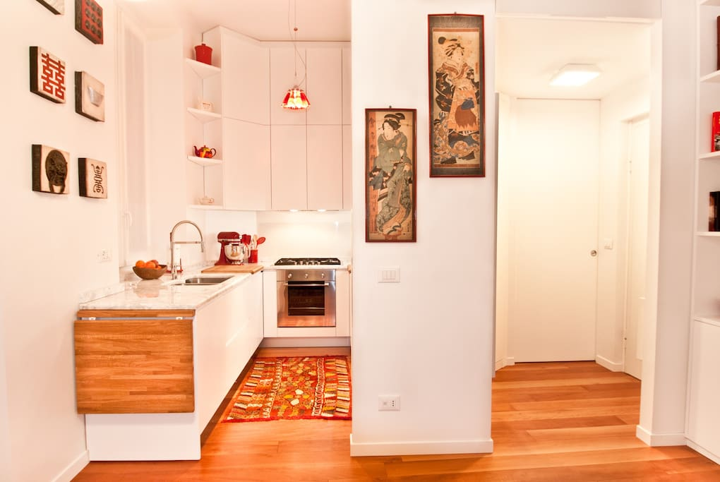 Kitchen Area on the left with Asian Artwork and Ingo Maurer's famous Campari light. On the right the entrance.