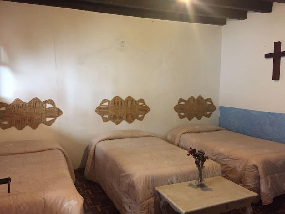 Tres camas individuales, t.v. cajonera, ropero con perchas