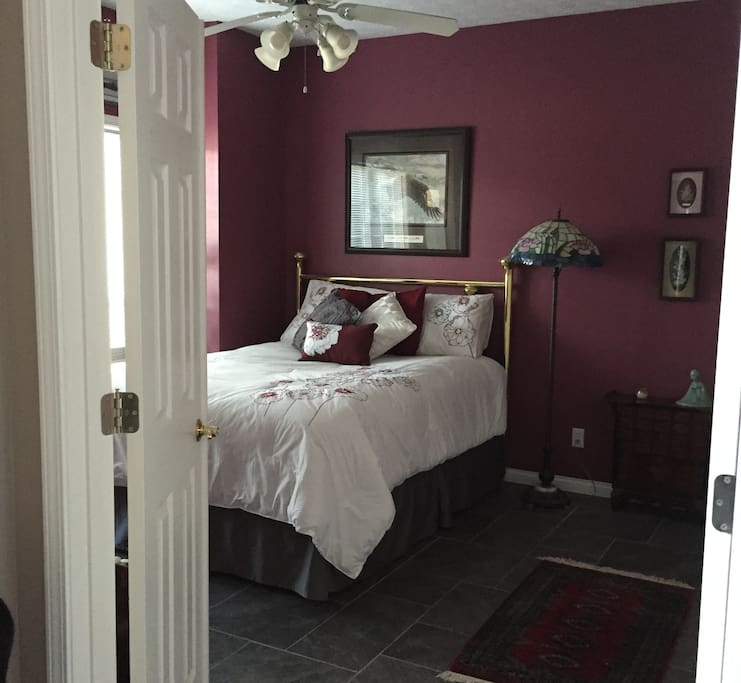 Queen bed with ceiling fan, closet and adjoining bath.