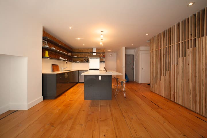 Open living and kitchen area. Stairs to the right. Pocket door behind kitchen goes to office area. Grey metal door is the entrance to apt. White door to the right goes to the basement.