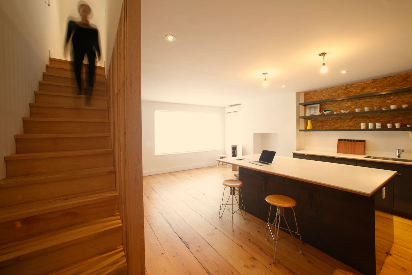 Open living and kitchen area. Stairs go up to bedrooms and large bathroom.