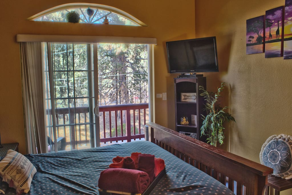 Bedroom with Queen bed, flat screen smart TV and private deck outside.