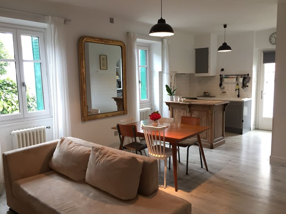 Salon et cuisine ouverte avec porte vers le jardin et la terrasse