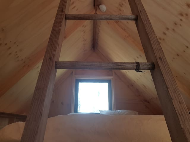 An old ladder access to the sleeping platform and double bed with crisp, clean linen