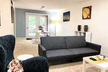 Living room is bright with plenty of natural light, and is equipped with 49-inch flat screen LED tv with cable channels.