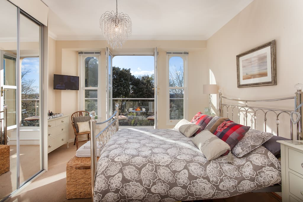 Spacious king size bedroom with large windows opening onto a balcony where you can enjoy coffee & croissants