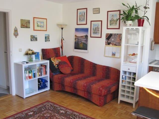 Chaiselongue als Ruhe- oder Leseecke mit Blick zum TV-Gerät -darunter befindet sich ein Stauraum für Reisetaschen