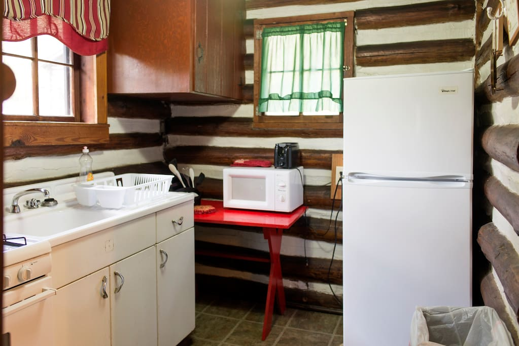 full kitchen with microwave, fridge and gas stove