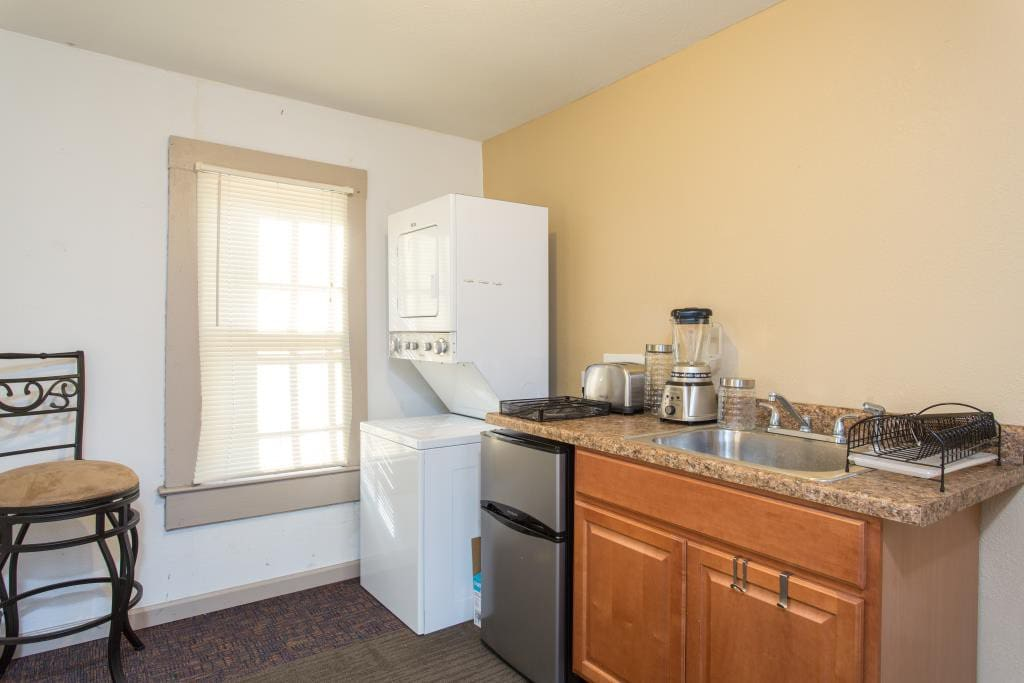 Kitchenette with washer/dryer, microwave, cabinet-top pressure oven, dishes