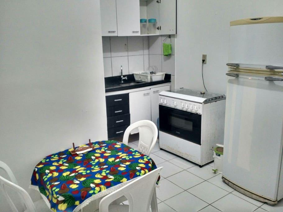 Cozinha com louça e equipamentos básicos.