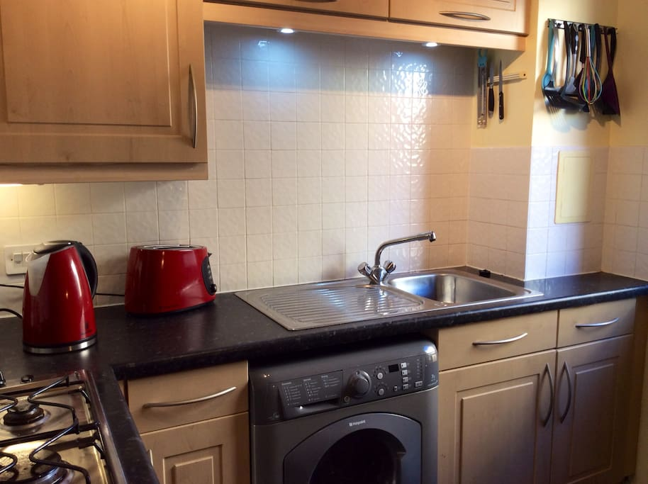 Fully equipped kitchen with hob, microwave, kettle, toaster and washing machine.