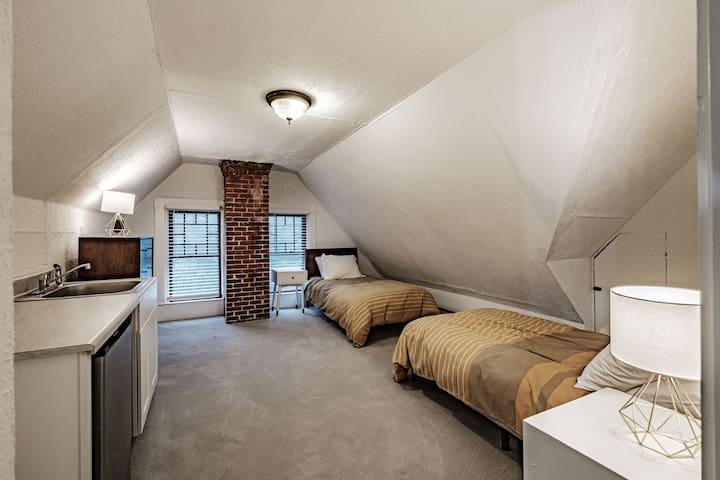Third floor bedroom with 2 twin beds, sink and mini-fridge.