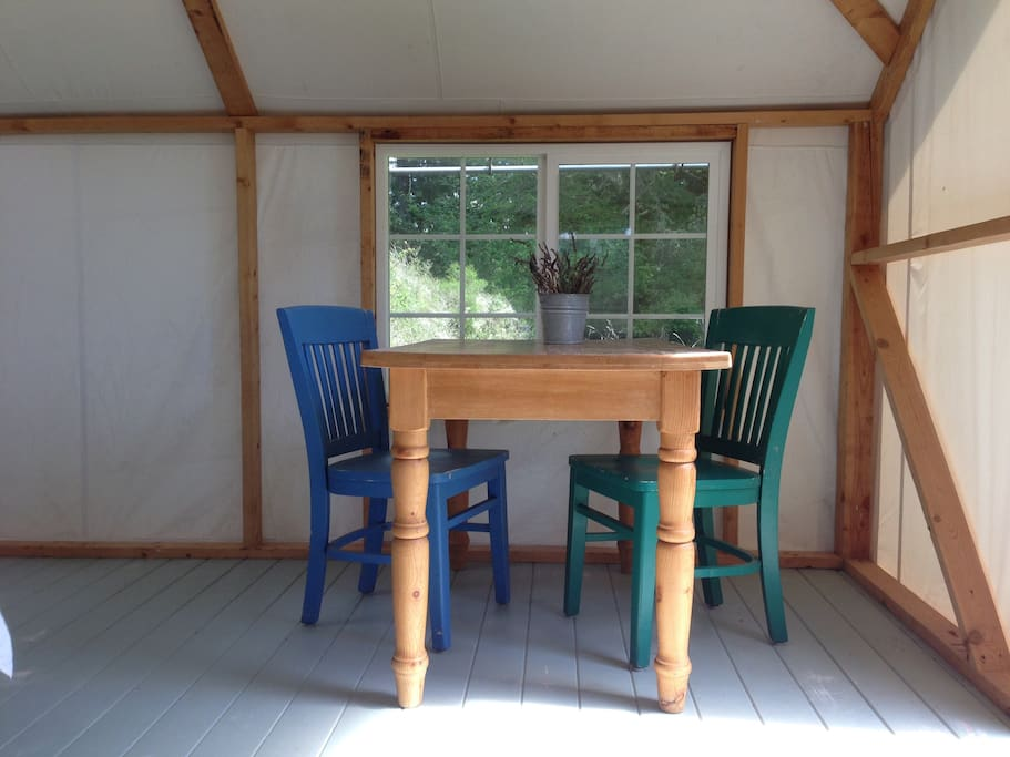 A table and chairs for meals, a glass of wine, or to write a poem. All the windows (and the door) have screens and provide a lovely breeze.