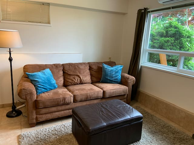 Living room area with La-Z-Boy Microfibre couch with queen sized 30 second pump  up mattress.  Super comfy!  Brand new TV with access to Netflix for your entertainment needs.