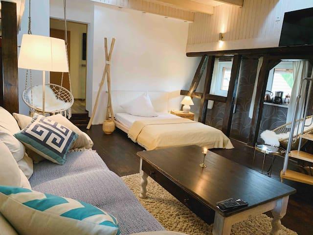 Blick vom Sofa auf das Bett im unteren Teil der Loft und auf dem Fernseher oben rechts