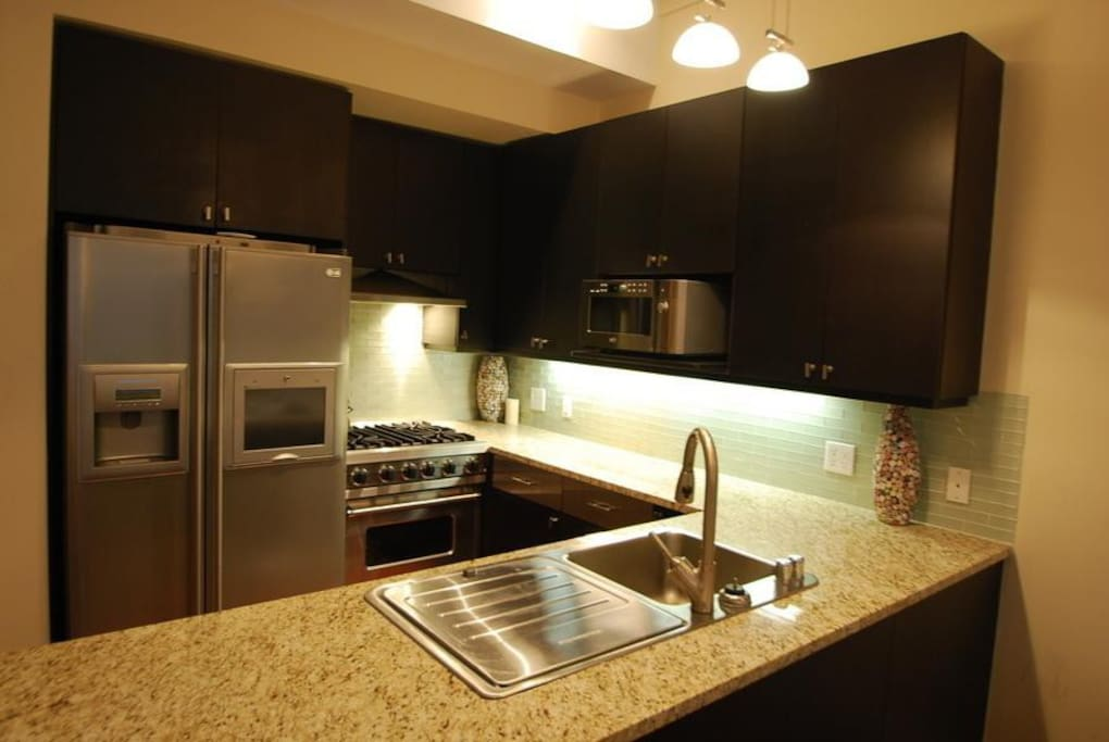 The sleek open kitchen is equipped with top-of-line stainless steel appliances, including a Viking stove, in-sink dishwasher, wine fridge, an LG refrigerator.
