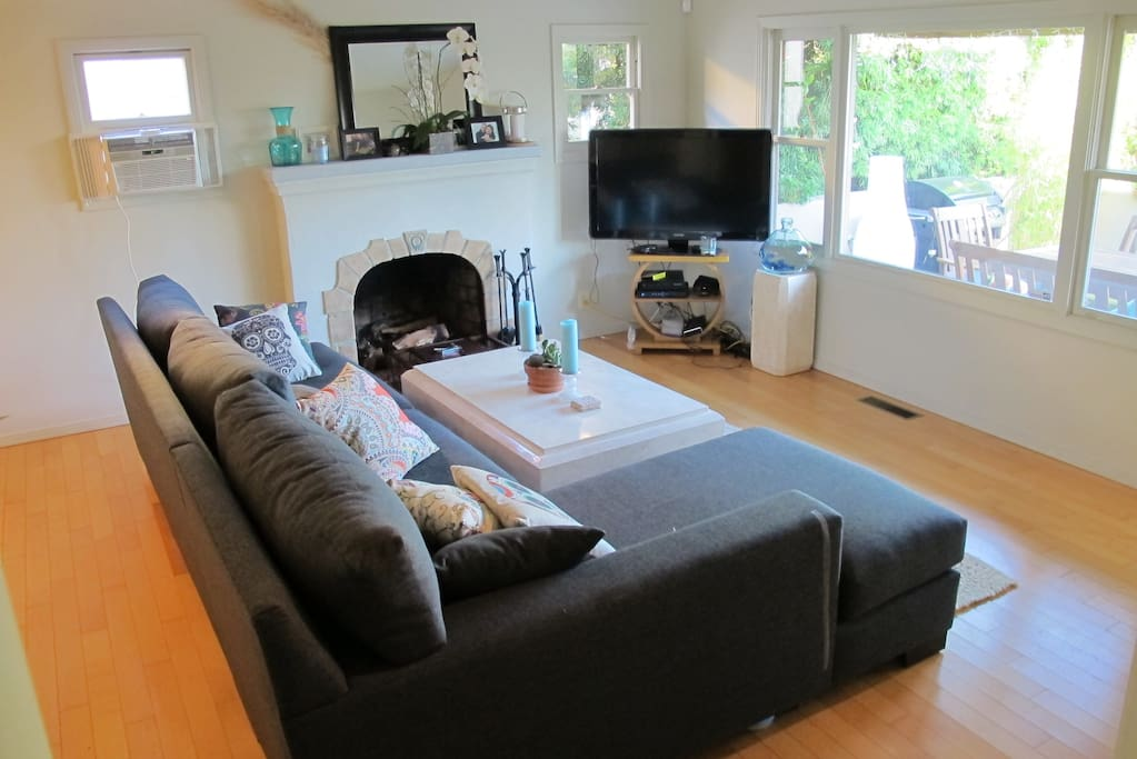 Large comfortable living room, with large couch and coffee table, looking over the Patio to the Channel Islands