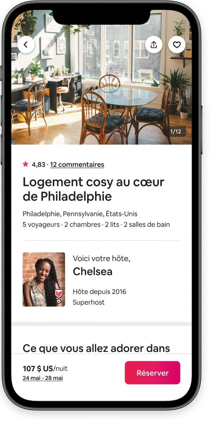 Un écran de paiement pour les voyageurs dans l'application Airbnb avec une photo d'une cuisine, des informations sur l'hôte et un bouton «Réserver».