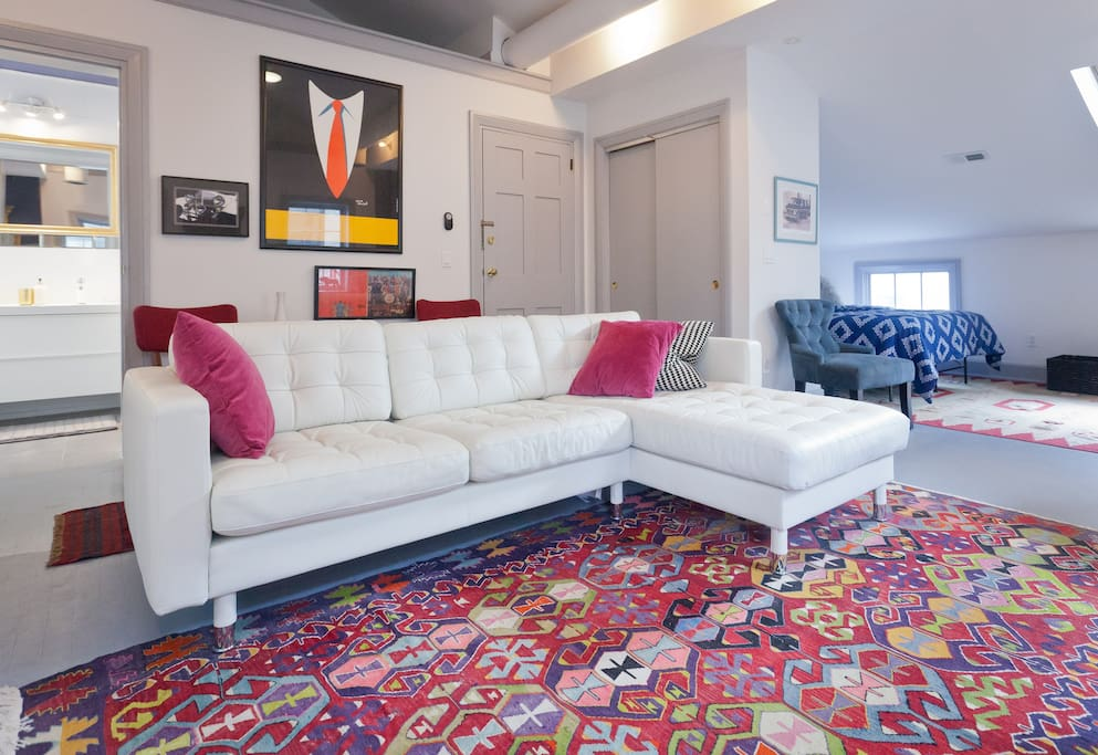 Your apartment is a light-filled space with an open floor plan, anchored by a plush white leather contemporary sofa and a collection of antique and vintage tribal flatweave rugs (kilims)
