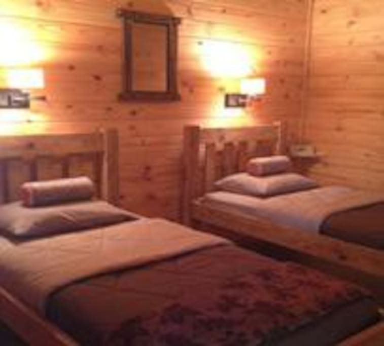 Quaint two beds in each private lodge cabin room made of oak.