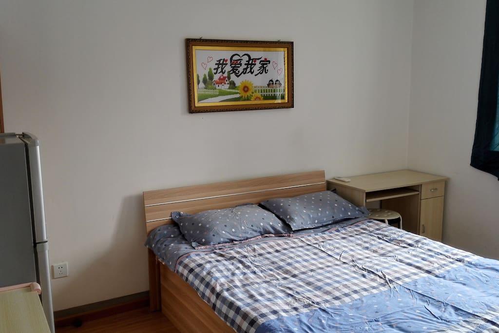 一张1.5米双人床,墙上挂着我爱我家的手工十字绣,有2张书桌,1个衣柜,1个双门冰箱,可提供房客单独使用。