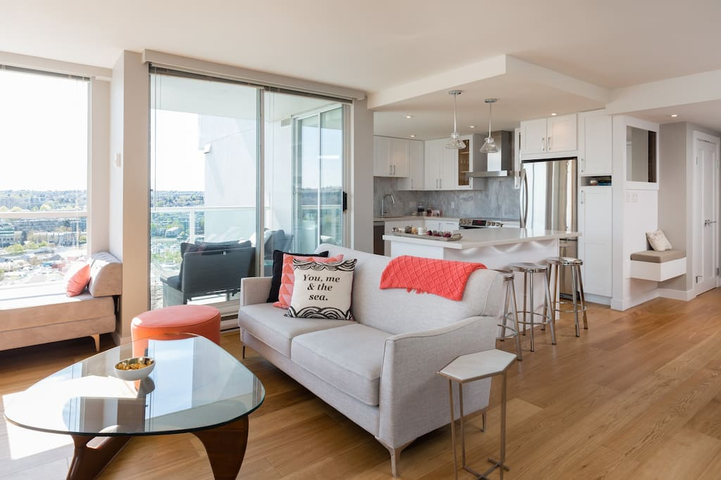 The open concept of the apartment is one of the best features. It is bright, roomy and very modern. In this photo you can see the kitchen with stainless steel appliances in the background.