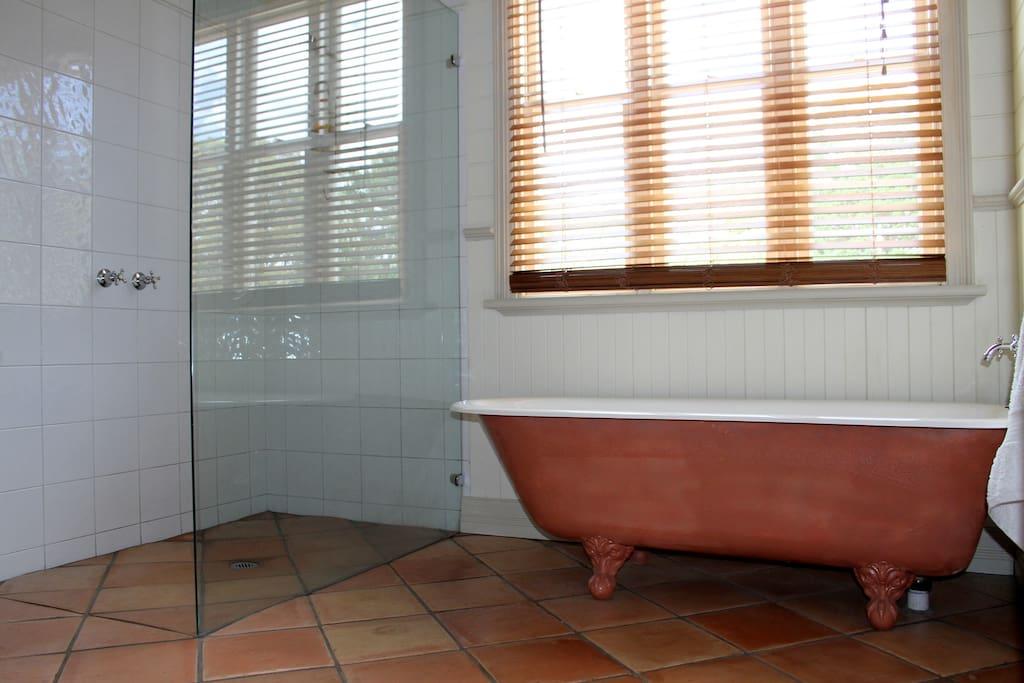 Spacious bathroom with clawfoot bath and walk-in shower.