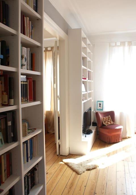 Das Wohnzimmer: Die Flügeltür zwischen Wohn- und Schlafzimmer kann geschlossen werden. Und  die Bücher in den Regalen warten sehnsüchtig auf neue Leser.