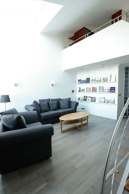 Spacious living room with high ceilings,  comfortable sofas, amazing view of mountain Esja and some cool books about Iceland.