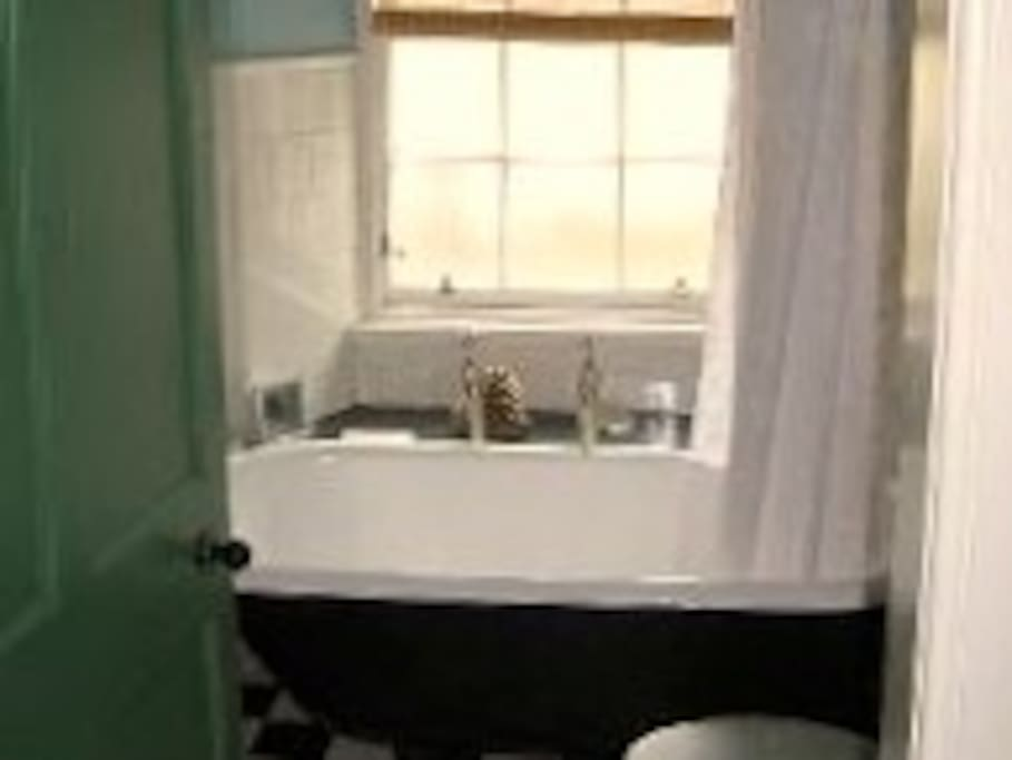 Bathroom with roll top bath and shower