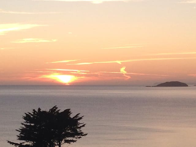 Looe Island with the sun setting next to her.