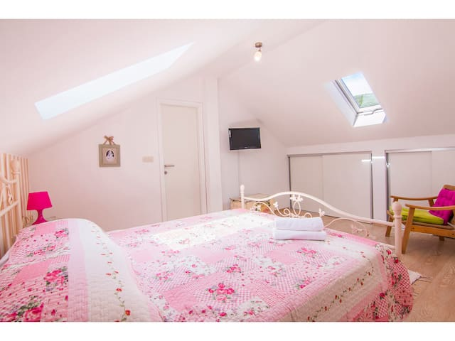 Double bed bedroom with TV and bathroom with shower, toilet, sink and washing machine