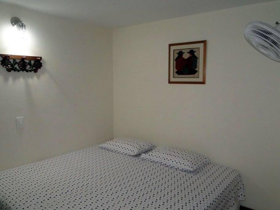 Habitación principal con cama doble, baño privado, Closet, televisor, ventilador.