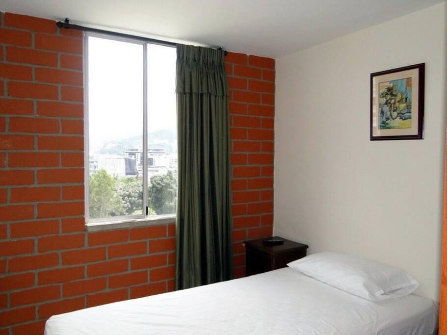 Habitación secundaria con cama sencilla, mesa auxiliar, closet, televisor y ventilador.