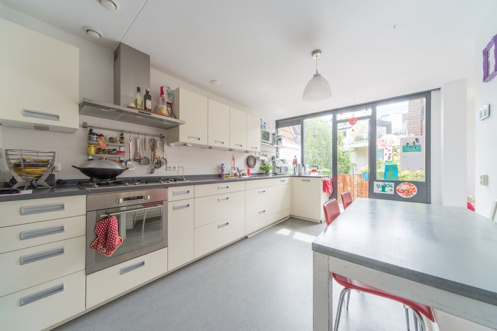 spacious kitchen with oven, microwave, big fridge and terras on the side