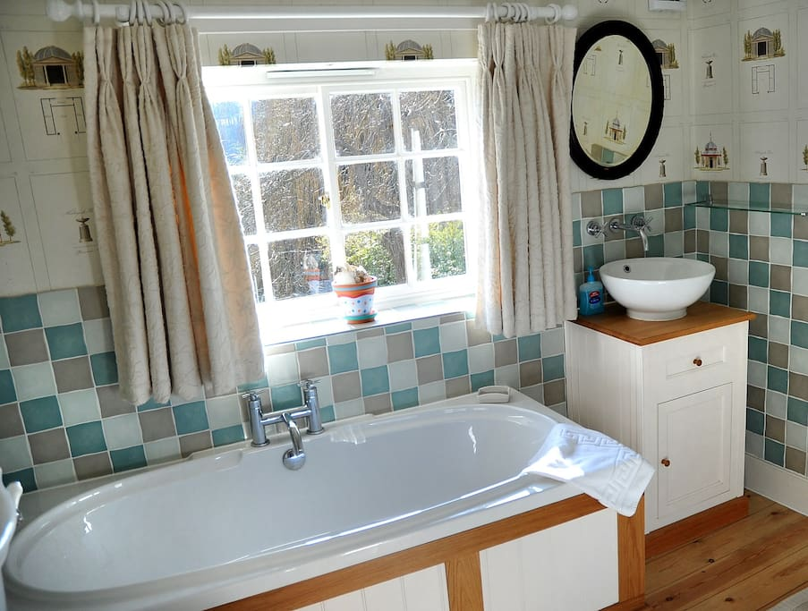 South facing bathroom with bath and free-standing electric shower