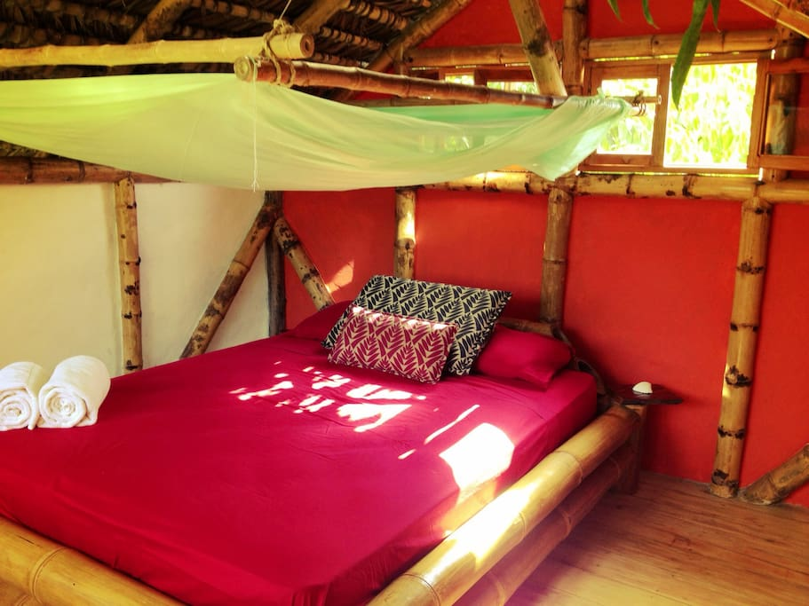 New queen mattresses & breezy mosquito nets on a jungle-y bamboo frame