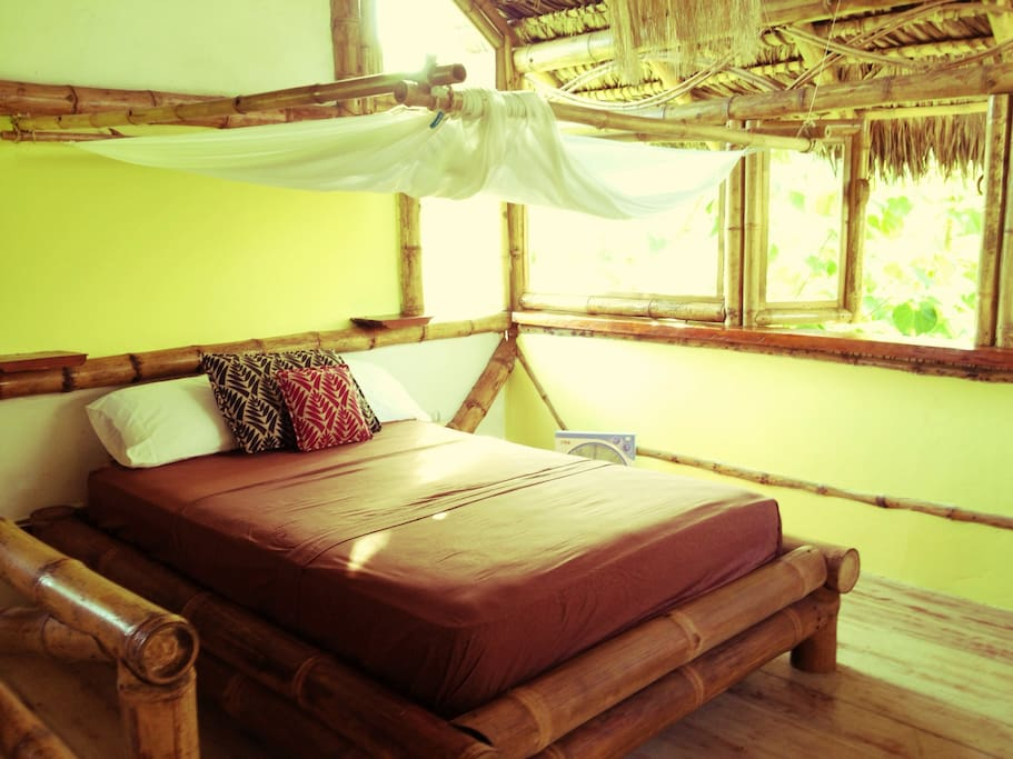 Upstairs double bed with new mattress & breezy mosquito net on jungle-y bamboo frames