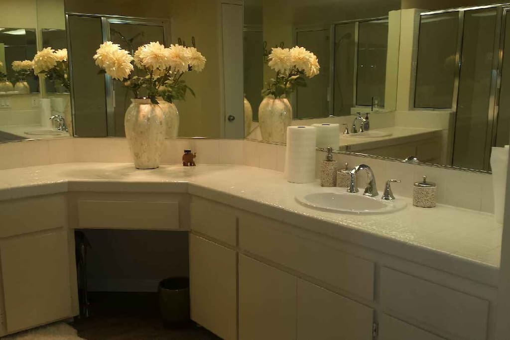 dual sinks, tub, and private toilett in master bath