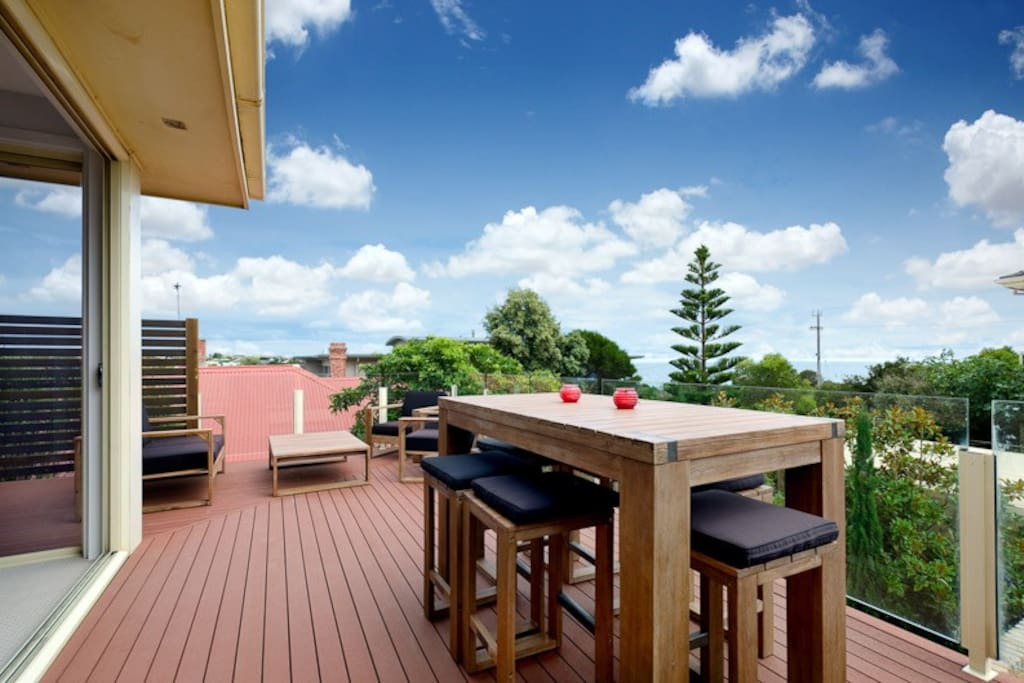 Spacious decked balcony with BBQ and new outdoor lounge furniture with matching bench height dining setting