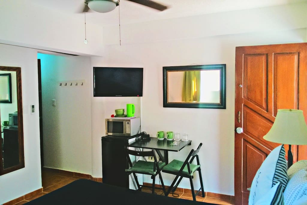 Spacious room with A/C, 32 inch TV, fridge, small table, coffee machine, microwave and  closet in the back