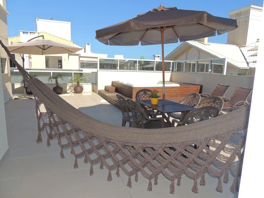 Área externa com churrasqueira, jacuzzi, espreguiçadeiras, mesa com cadeiras e ombrelone