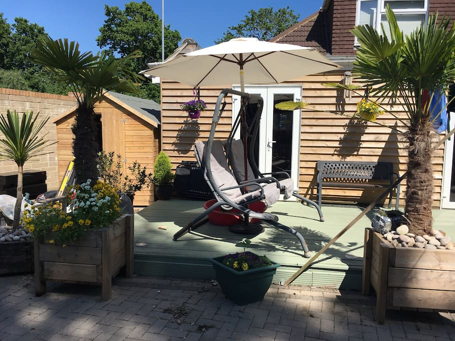 Beautiful swing boat & decking with bench seat & table & chairs that seats 6  with parosol