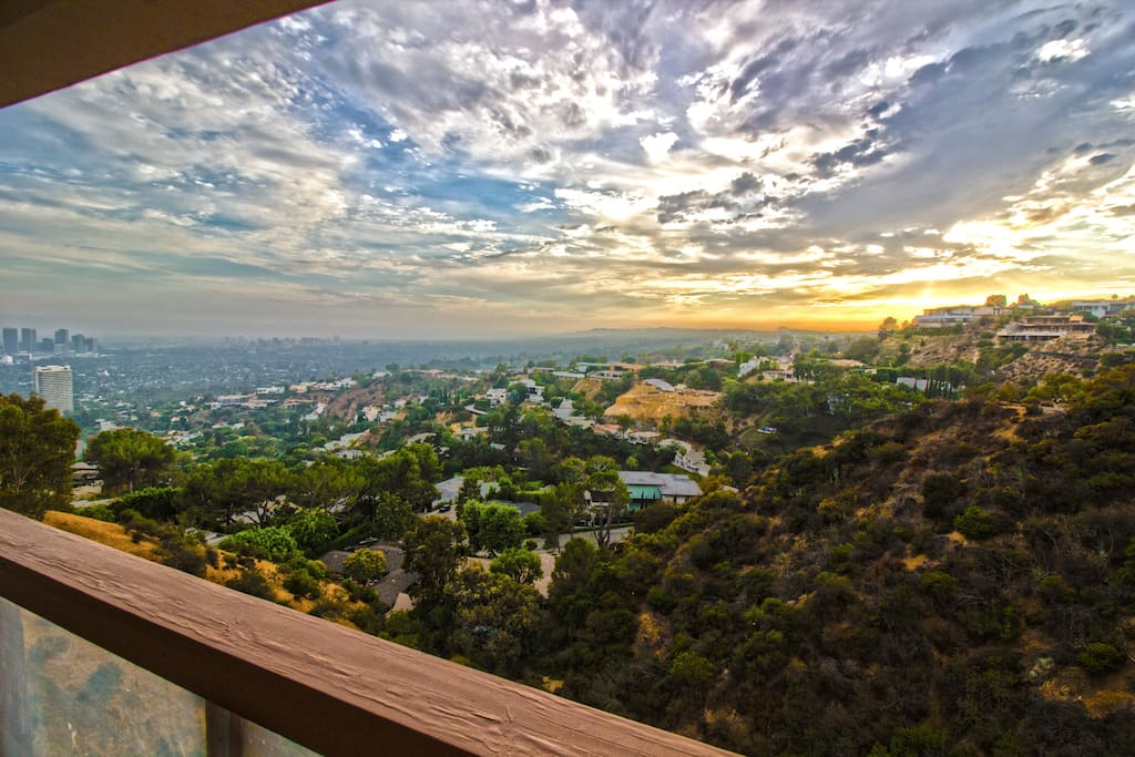 Top Floor Balcony - Sunset pic - balcony spans across entire house with multiple sliding doors and doors along living room, family room, and kitchen