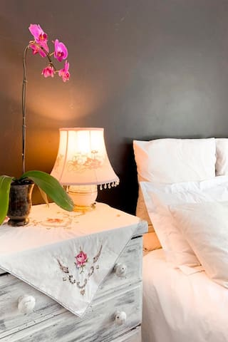 A convenient bed lamp on a chest of drawers in the main bedroom, providing a warm & cozy atmosphere, together with some fresh flowers....