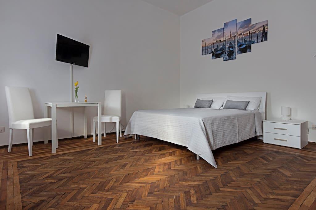 camera da letto con TV e tavolo per poter lavorare